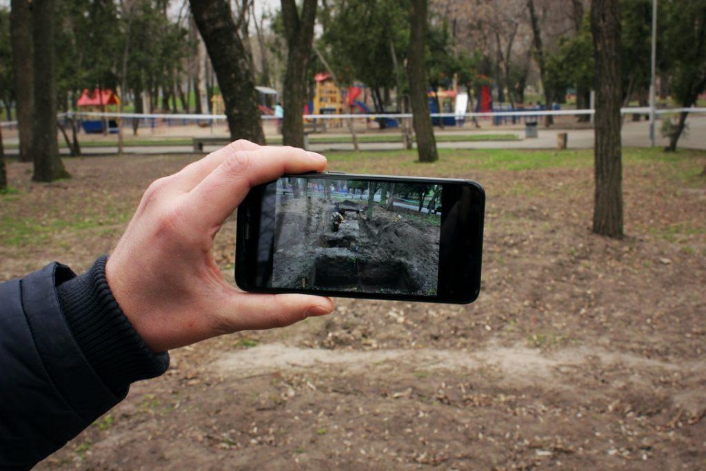 Артём Костюк показывает на телефоне место, где ищут могилу Александра Поля