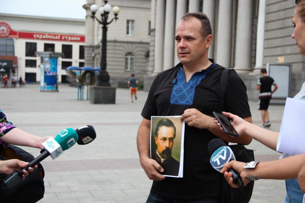 екскурсовод Ігор Кочергін з портретом Олександра Поля