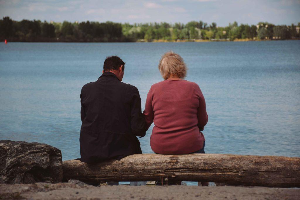 Пара сидить на березі річки у парку біля Парусу