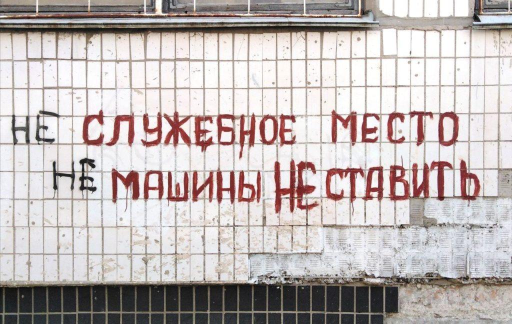 """Напис на стіні будинку: """"НЕ служебное место. НЕ машины НЕ ставить"""". Первые два """"не"""" дописаны каким-то шутником"""
