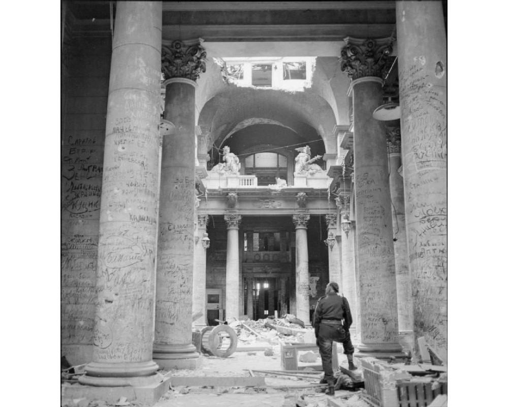 Солдат стоит внутри Рейхстага и осматривает колонны, почти до потолка покрытые граффити.
