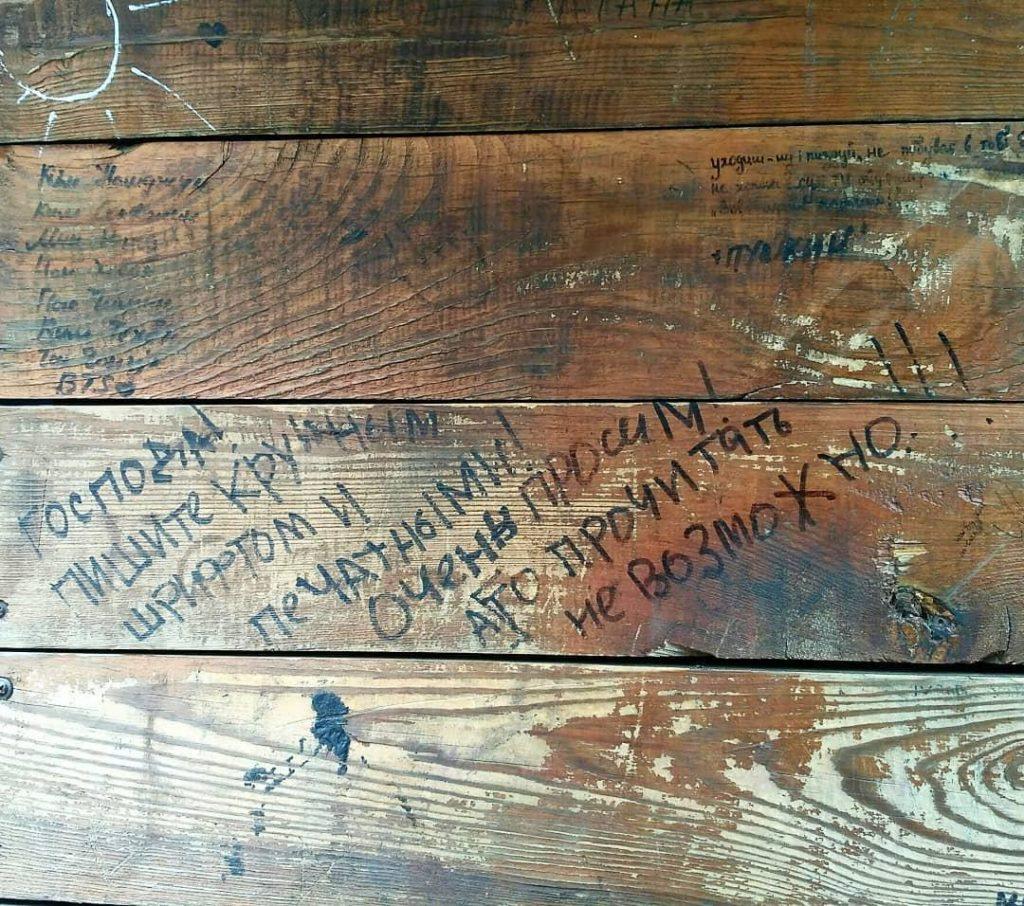 """Надпись на деревянных досках: """"Господа! Пишите крупным шрифтом и печатными! А то прочитать невозможно!"""""""