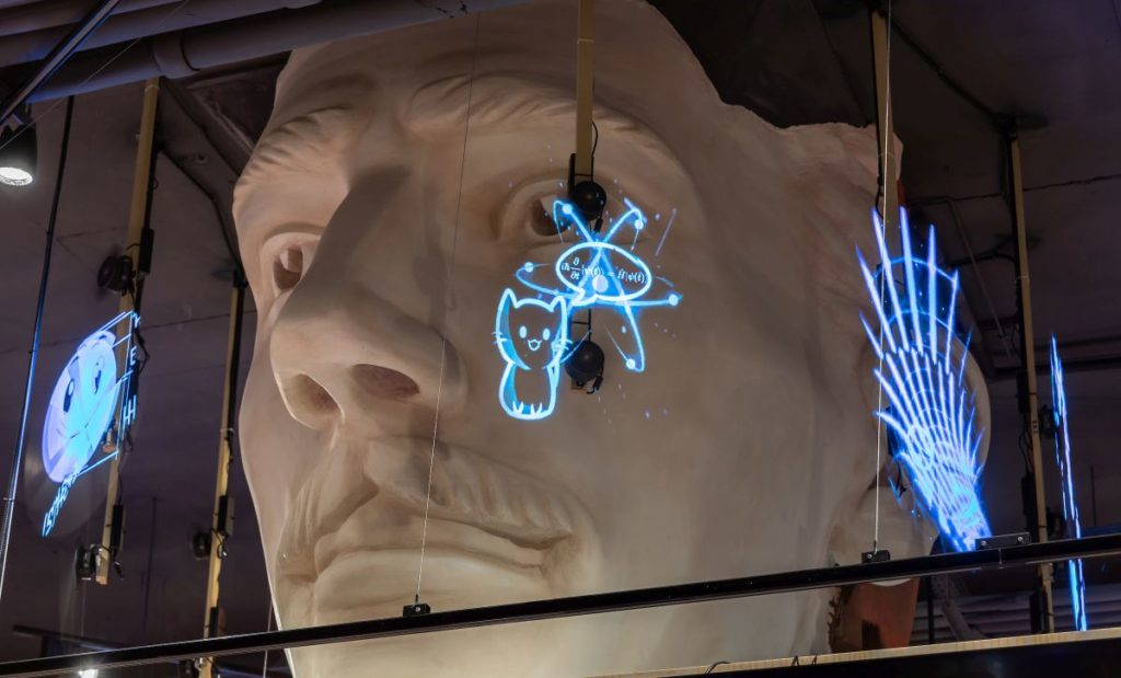 Велика скульптурна голова, на яку транслюються голографічні формули та зображення