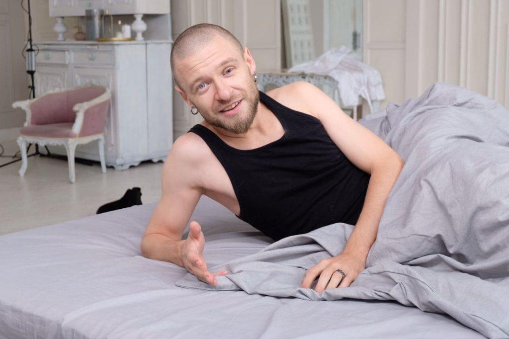"""На съемках ролика для """"Бийся як дівчина"""": мужчина, лежа в постели, рассказывает что-то на камеру."""