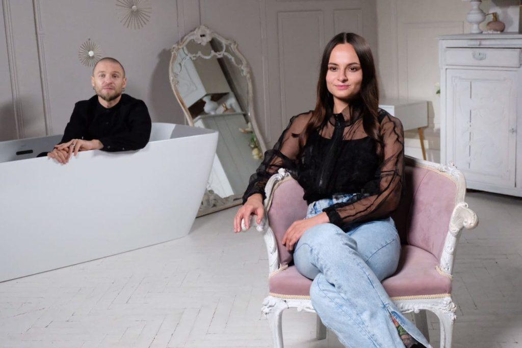 На переднем плане девушка сидит в кресле, на заднем - одетый парень в ванне. Фото со съемочной площадки.