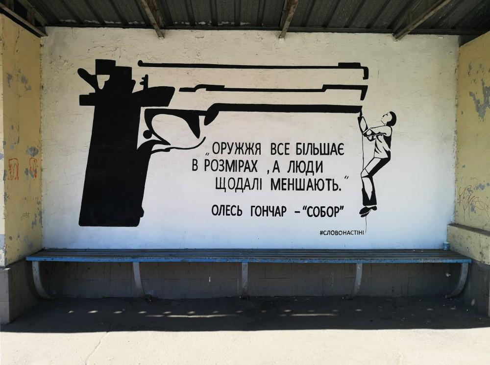 """Малюнок на зупинці: Великий пістолет і маленький чоловічок, що звисає з нього. Цитата Олеся Гончара: """"Оружжя все більшає в розмірах, а люди дедалі меншають"""""""