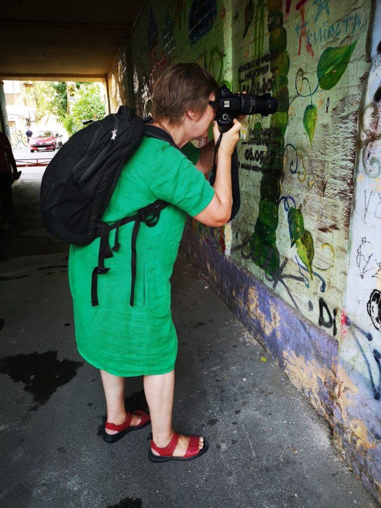 Женщина с рюкзаком фотографирует стену в арке киевской многоэтажки