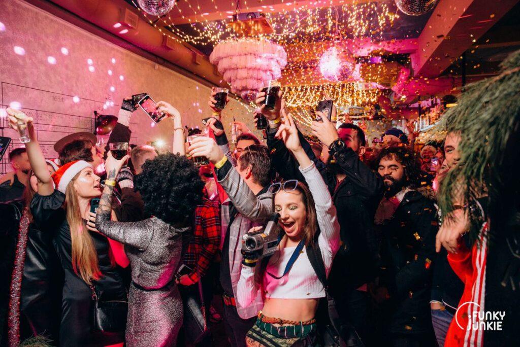 Гости танцуют и снимают всё на телефоны и старые видеокамеры.